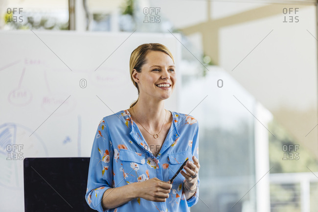Happy mid adult businesswoman holding pen while standing in brightly lit office