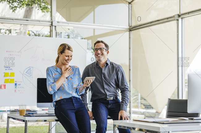 Happy businessman with female colleague using smartphone while leaning on desk in office
