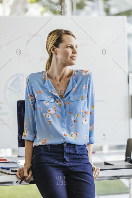 Thoughtful businesswoman leaning on desk in brightly lit office