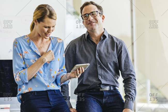Smiling businessman with female colleague using smartphone while standing in brightly lit office