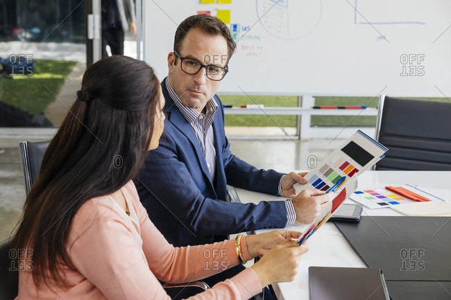 Confident businessman discussing over color swatch with female colleague in office