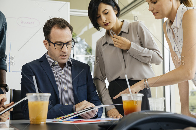 Businessman discussing over color swatches with female colleagues at desk in brightly lit office