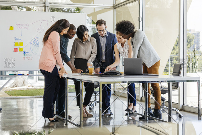 Full length of multiethnic business colleagues working at desk by window in bright office