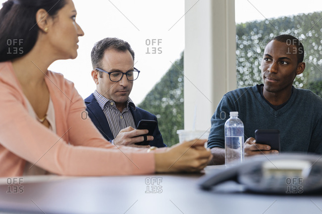 Businessman using smartphone while meeting with colleagues on conference room