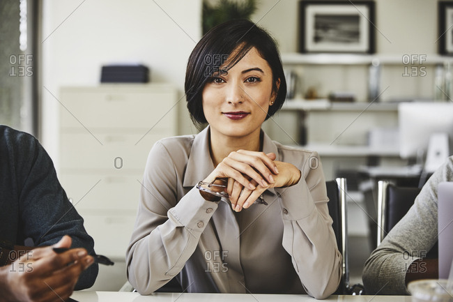 Portrait of confident young businesswoman sitting with hands clasped at desk in office