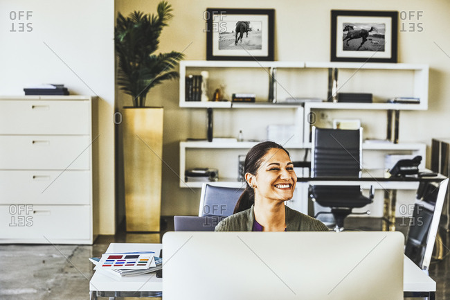 Mid adult businesswoman smiling while looking away in office