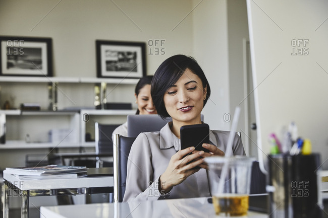 Young businesswoman using smart phone at desk in office