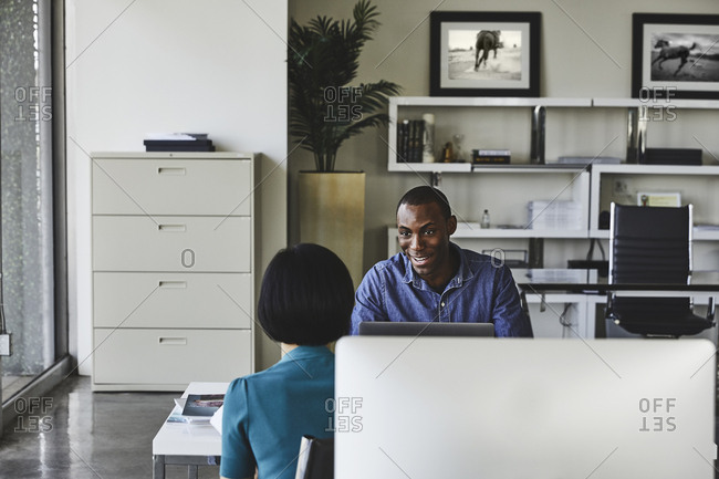 Young businessman communicating with female colleague in office