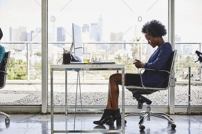 Full length side view of young businesswoman using mobile phone at desk in modern office