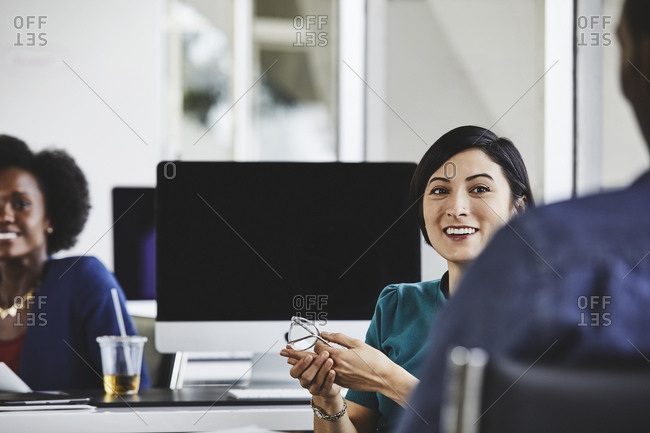 Young businesswoman smiling while sitting with colleagues in office