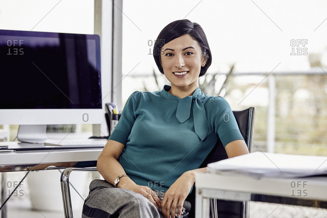 Young confident businesswoman with short hair sitting at desk in office