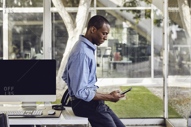 Side view of confident businessman using smart phone while leaning on desk in modern office