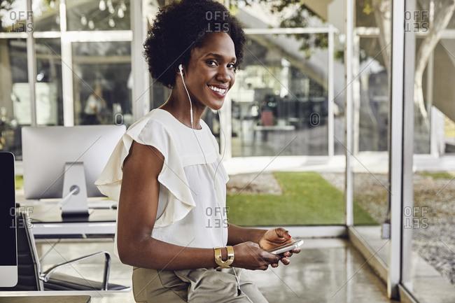 Portrait of confident businesswoman wearing earphones to communicate in office