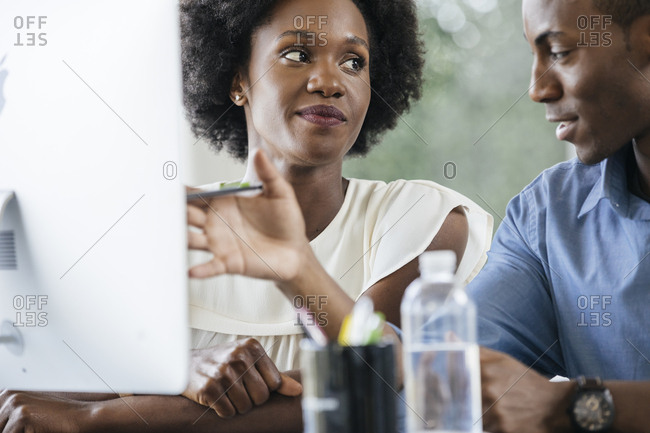 Young businesswoman looking at male colleague gesturing while discussing in office