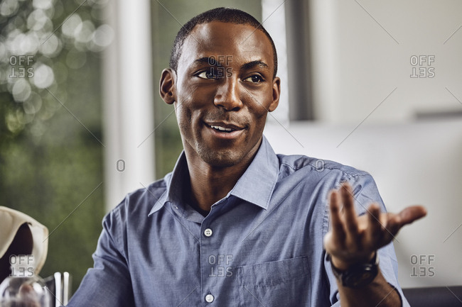 Smiling young businessman gesturing while looking away in office