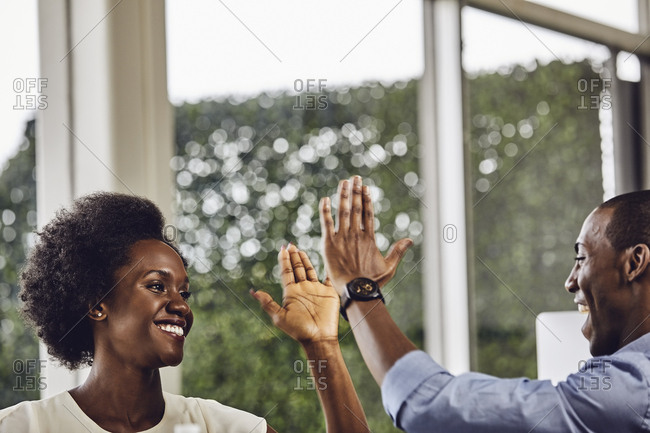 Happy male and female business colleagues giving high-five to each other at desk in office