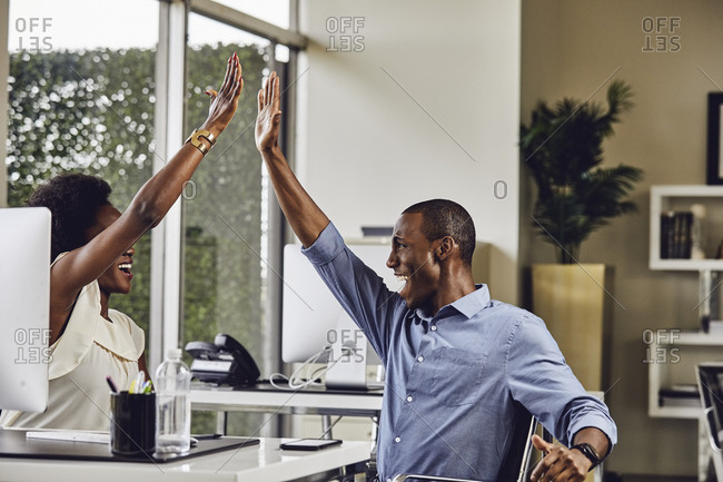 Happy male and female business people giving high-five to each other at desk in office