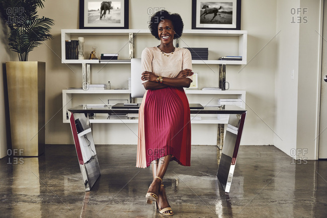 Full length of happy businesswoman with arms crossed leaning on desk in office