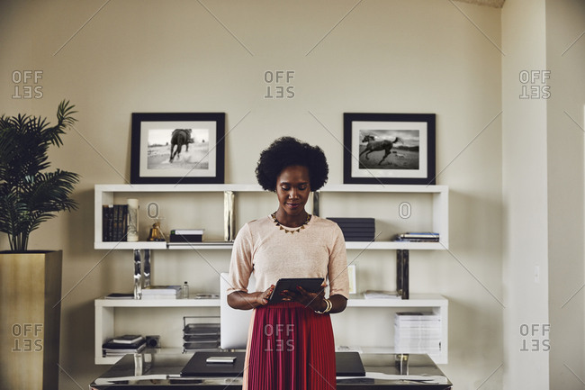 Young businesswoman using digital tablet while standing in office