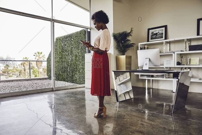 Full length side view of businesswoman using digital tablet while standing in office