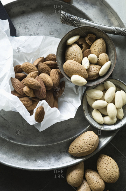 Peeled and whole almonds on tin plate