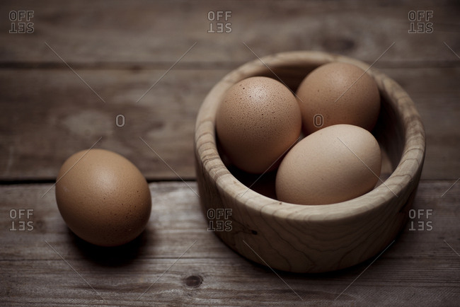 Organic brown eggs in a wooden bowl