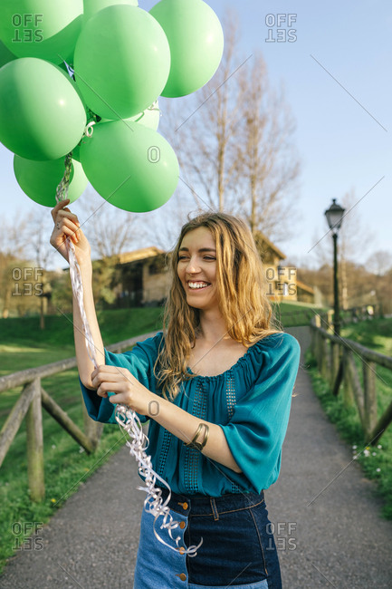 Portrait of laughing young woman with green balloons