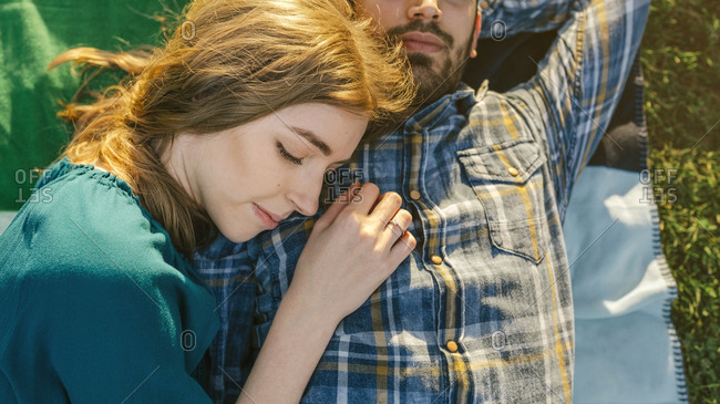 Young couple lying on blanket on a meadow