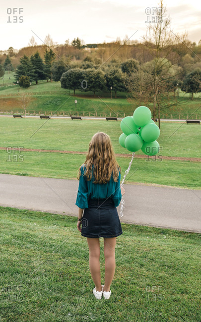 Back view of young woman with  green balloons standing on a meadow