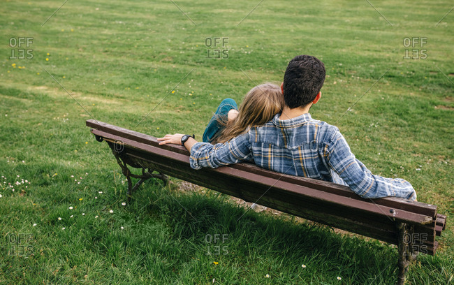 Back view of young couple sitting on bench on a meadow