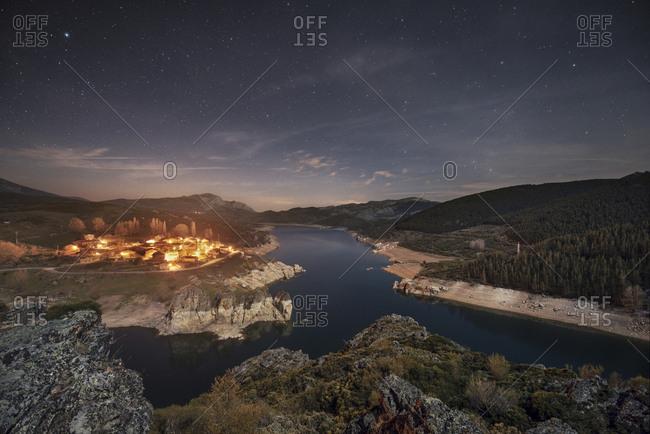 Spain- Castilla y Leon- Palencia- starry night over small village and lake Camporredondo