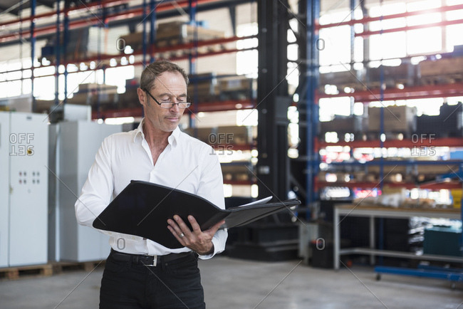 Man with documents on factory shop floor