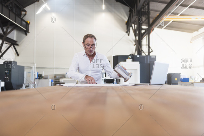 Man with plan- product and laptop on table in factory