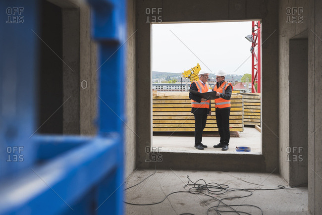 Two men wearing safety vests talking in building under construction