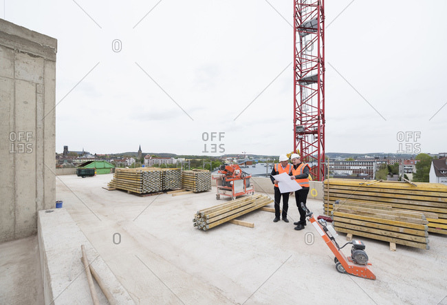 Two men with plan wearing safety vests talking on construction site