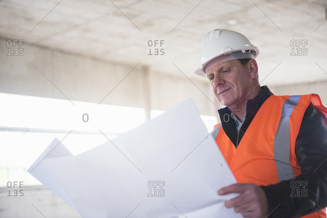 Man with plan wearing safety vest in building under construction