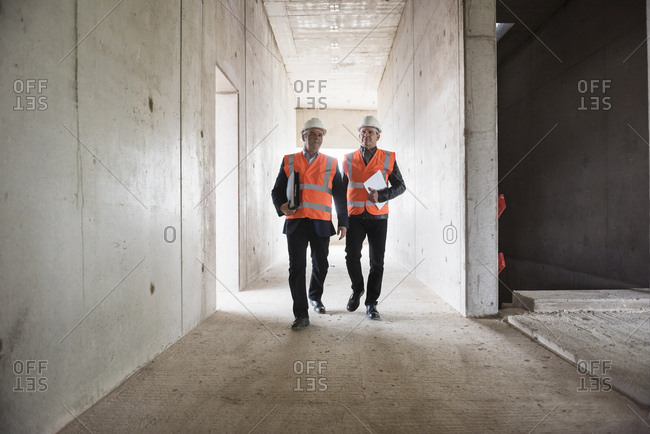 Two men wearing safety walking in building under construction