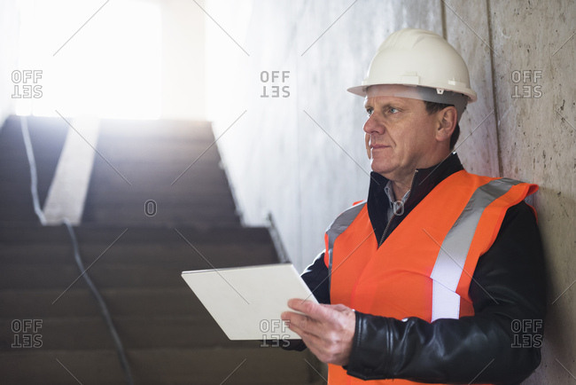 Man with tablet wearing safety vest in building under construction