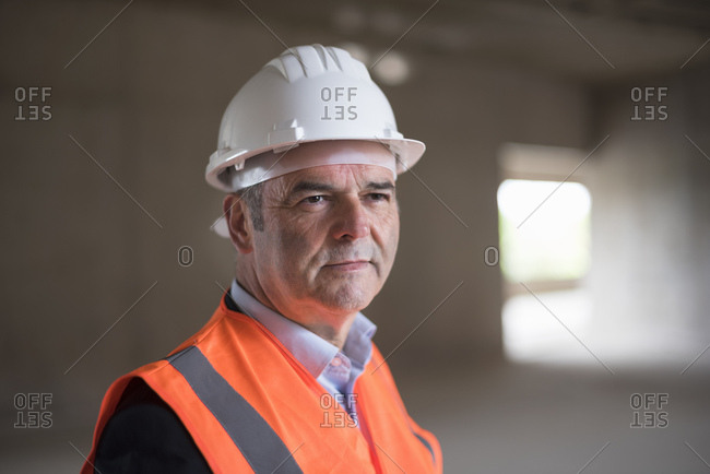 Portrait of man wearing safety vest in building under construction