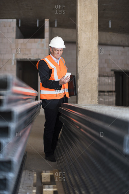 Man with cell phone wearing safety vest in building under construction