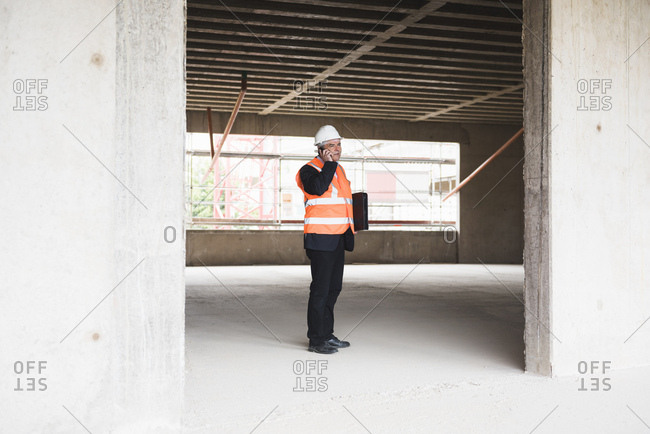 Man on the phone wearing safety vest in building under construction