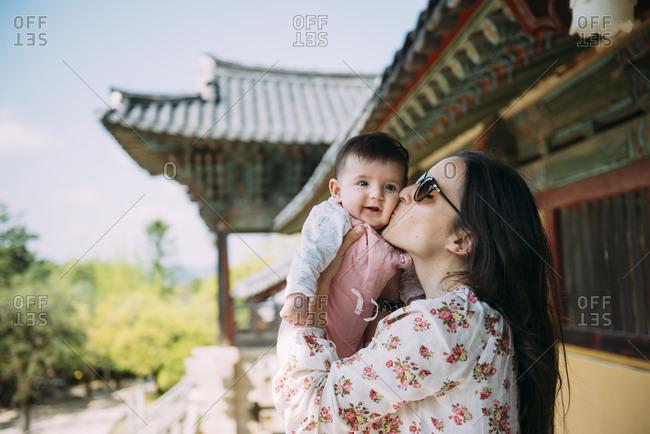 South Korea- Gyeongju- womankissing a baby girl in Bulguksa Temple