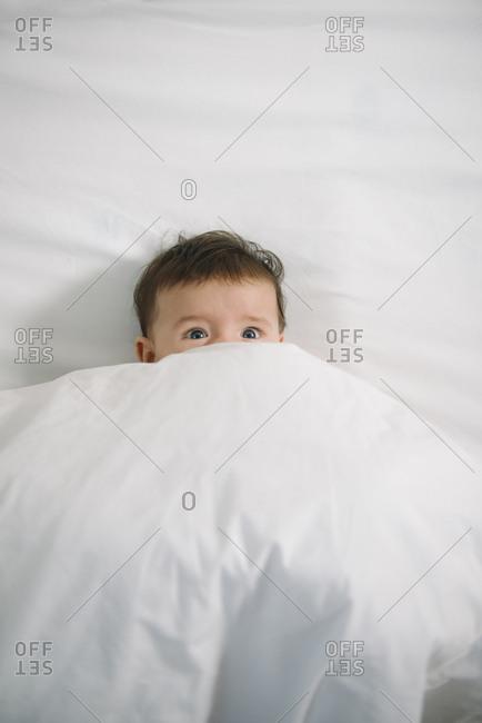 Portrait of scared baby girl lying under white blanket