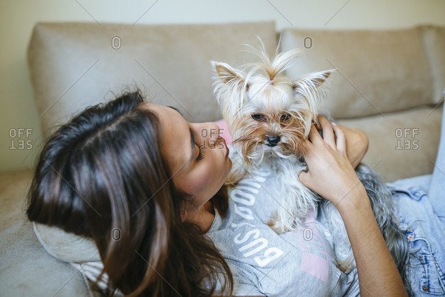 Woman lying on couch with her Yorkshire Terrier