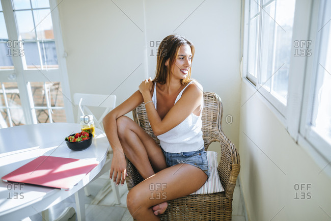Young woman sitting on basket-chair at home looking through window