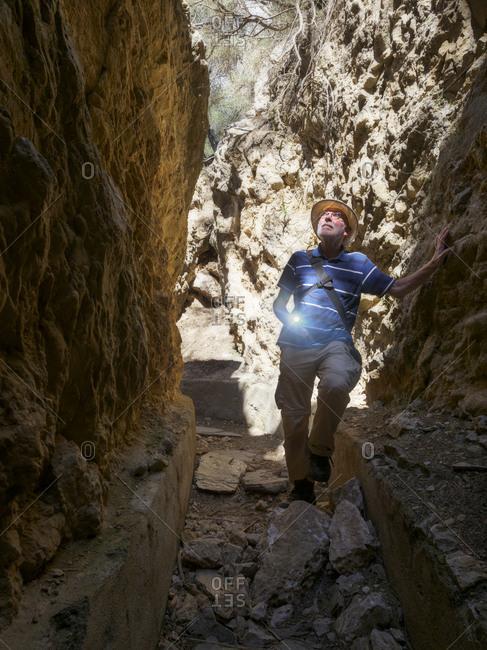 Spain- Sierra Nevada- Laujar de Andarax- senior man exploring old water canal