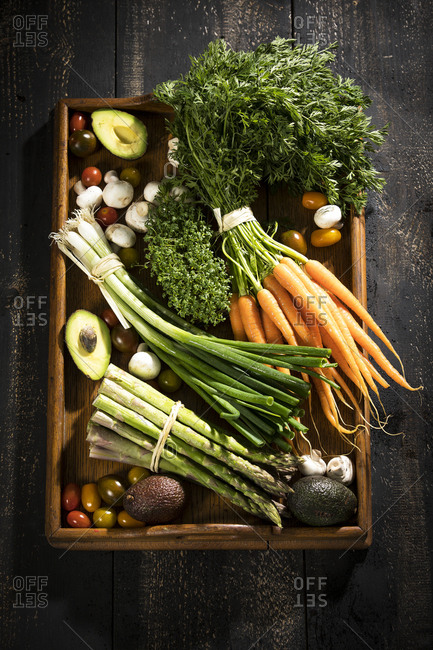 Various organic vegetables on dark wooden tray