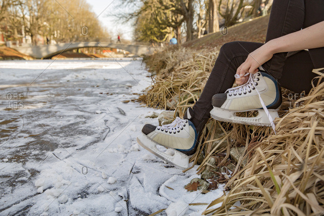 Close-up of woman putting on ice skates at canal
