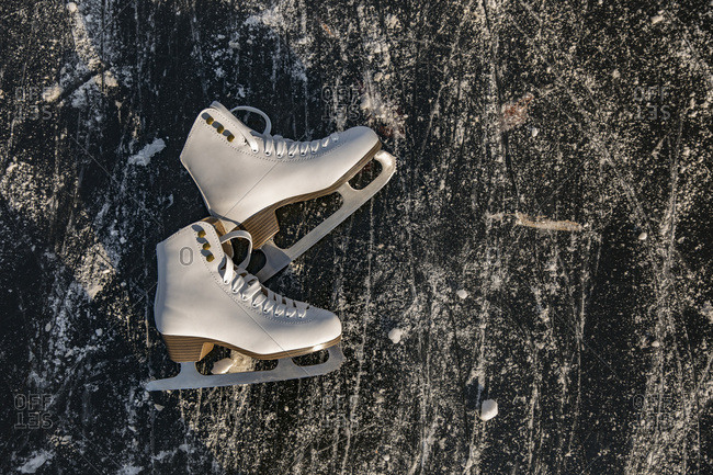 Ice skates lying on frozen water surface with skate traces
