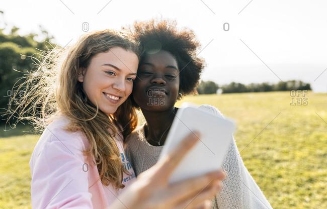 Two best friends making a selfie outdoors